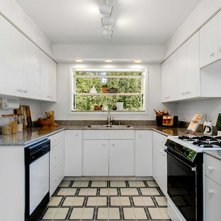 This is an example of a mid-sized midcentury u-shaped separate kitchen in Seattle with a drop-in sink, flat-panel cabinets, white cabinets, terrazzo benchtops, black appliances, linoleum floors and no island.