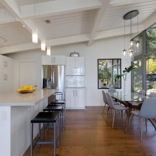 This is an example of a midcentury galley eat-in kitchen in Santa Barbara with flat-panel cabinets, white cabinets, stainless steel appliances, medium hardwood floors, with island, brown floor and grey benchtop.
