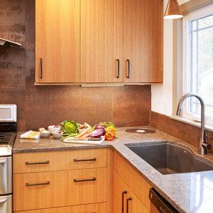 Inredning av ett 60 tals avskilt, litet grå grått l-kök, med en undermonterad diskho, släta luckor, skåp i ljust trä, bänkskiva i kvarts, stänkskydd med metallisk yta, stänkskydd i porslinskakel, rostfria vitvaror, linoleumgolv och grönt golv