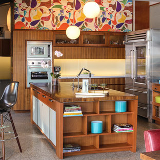 Design ideas for a midcentury l-shaped kitchen in Santa Barbara with flat-panel cabinets, stainless steel appliances, wood benchtops and medium wood cabinets.