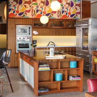 Diseño de cocina en L, retro, con armarios con paneles lisos, electrodomésticos de acero inoxidable, encimera de madera y puertas de armario de madera oscura