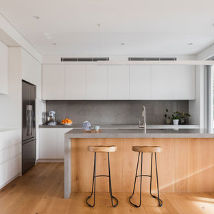 Photo of a large contemporary l-shaped open plan kitchen in Sydney with an undermount sink, white cabinets, quartz benchtops, grey splashback, stainless steel appliances, medium hardwood floors, with island, brown floor, grey benchtop and flat-panel cabinets.