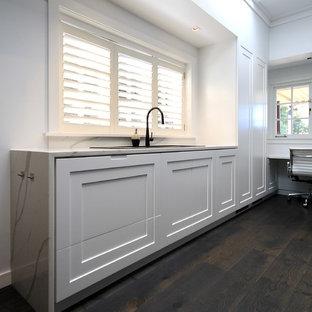 Ispirazione per un'ampia cucina minimalista con lavello da incasso, ante con bugna sagomata, ante nere, top in quarzo composito, paraspruzzi bianco, paraspruzzi in lastra di pietra, elettrodomestici neri, parquet scuro, 2 o più isole, pavimento nero e top bianco