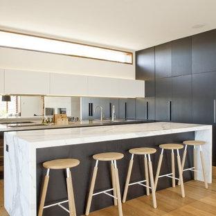 Zweizeilige, Große Moderne Küche mit flächenbündigen Schrankfronten, dunklen Holzschränken, Marmor-Arbeitsplatte, Rückwand aus Spiegelfliesen, hellem Holzboden und Kücheninsel in Sydney