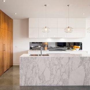 Bild på ett mellanstort funkis kök, med en undermonterad diskho, släta luckor, vita skåp, marmorbänkskiva, stänkskydd med metallisk yta, glaspanel som stänkskydd, betonggolv och en köksö