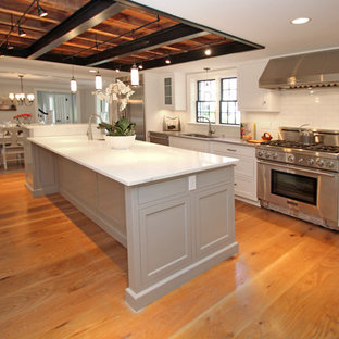 ボストンの広いおしゃれなキッチン (シェーカースタイル扉のキャビネット、ステンレスキャビネット、アンダーカウンターシンク、人工大理石カウンター、白いキッチンパネル、サブウェイタイルのキッチンパネル、シルバーの調理設備、無垢フローリング、茶色い床) の写真