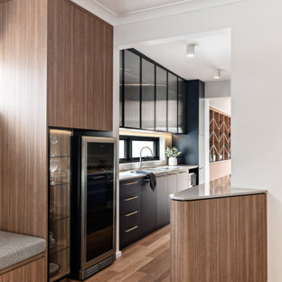 Design ideas for a mid-sized contemporary galley separate kitchen in Sydney with a double-bowl sink, blue cabinets, quartz benchtops, grey splashback, engineered quartz splashback, stainless steel appliances, medium hardwood floors, no island, brown floor and grey benchtop.