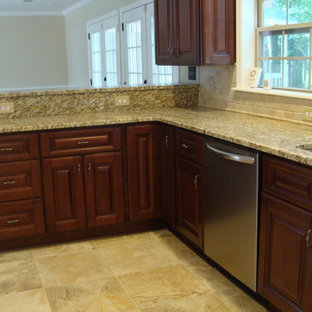 Design ideas for a large traditional galley open plan kitchen in Atlanta with an undermount sink, raised-panel cabinets, dark wood cabinets, granite benchtops, beige splashback, stone tile splashback, stainless steel appliances, porcelain floors and a peninsula.