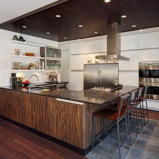 Kitchen - contemporary u-shaped dark wood floor kitchen idea in Milwaukee with flat-panel cabinets, white cabinets, white backsplash, stainless steel appliances and an undermount sink