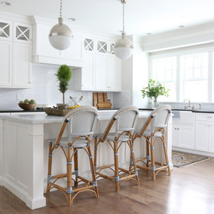 Beach style kitchen remodeling - Kitchen - beach style l-shaped medium tone wood floor kitchen idea in Salt Lake City with a farmhouse sink, shaker cabinets, white cabinets, white backsplash, subway tile backsplash and an island