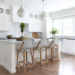 Beach style kitchen remodeling - Kitchen - beach style l-shaped medium tone wood floor kitchen idea in Salt Lake City with a farmhouse sink, shaker cabinets, white cabinets, white backsplash, subway tile backsplash and an island