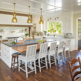 Farmhouse eat-in kitchen ideas - Example of a country l-shaped dark wood floor eat-in kitchen design in Salt Lake City with a farmhouse sink, shaker cabinets, white cabinets, stainless steel appliances and an island