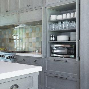 Amerikansk inredning av ett mycket stort kök, med luckor med profilerade fronter, grå skåp, blått stänkskydd, stänkskydd i keramik, integrerade vitvaror och flera köksöar