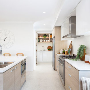 Photo of a beach style galley eat-in kitchen in Brisbane with a double-bowl sink, flat-panel cabinets, medium wood cabinets, white splashback, mosaic tile splashback, stainless steel appliances, with island, beige floor and white benchtop.