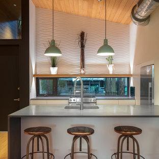 Idéer för små funkis linjära grått kök med öppen planlösning, med en integrerad diskho, släta luckor, vita skåp, bänkskiva i betong, fönster som stänkskydd, rostfria vitvaror, ljust trägolv, en halv köksö och flerfärgat golv