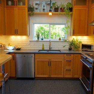 ポートランドの小さいモダンスタイルのおしゃれなキッチン (アンダーカウンターシンク、シェーカースタイル扉のキャビネット、淡色木目調キャビネット、コンクリートカウンター、白いキッチンパネル、セラミックタイルのキッチンパネル、シルバーの調理設備の、リノリウムの床、アイランドなし) の写真