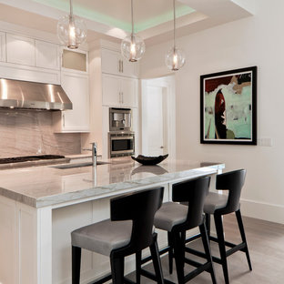 Mid-sized transitional open concept kitchen ideas - Open concept kitchen - mid-sized transitional u-shaped light wood floor open concept kitchen idea in Miami with an undermount sink, recessed-panel cabinets, white cabinets, granite countertops, gray backsplash, stainless steel appliances and an island