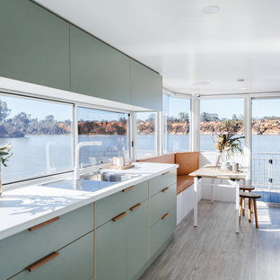 Design ideas for a beach style single-wall eat-in kitchen in Other with a drop-in sink, flat-panel cabinets, green cabinets, window splashback, panelled appliances, no island, beige floor and white benchtop.