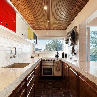 Small midcentury galley eat-in kitchen in Auckland with a drop-in sink, recessed-panel cabinets, dark wood cabinets, terrazzo benchtops, white splashback, brick splashback, white appliances, dark hardwood floors, no island and brown floor.