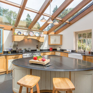 Rural l-shaped kitchen in Other with a belfast sink, shaker cabinets, medium wood cabinets, white splashback, integrated appliances, an island and grey floors.