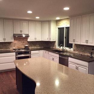 デトロイトの中くらいのトランジショナルスタイルのおしゃれなキッチン (アンダーカウンターシンク、レイズドパネル扉のキャビネット、白いキャビネット、クオーツストーンカウンター、マルチカラーのキッチンパネル、レンガのキッチンパネル、シルバーの調理設備、濃色無垢フローリング、茶色い床) の写真