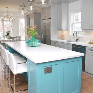 トロントの中サイズのトラディショナルスタイルのおしゃれなキッチン (アンダーカウンターシンク、落し込みパネル扉のキャビネット、グレーのキャビネット、クオーツストーンカウンター、白いキッチンパネル、石タイルのキッチンパネル、シルバーの調理設備の、テラコッタタイルの床) の写真