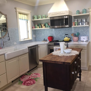 Mid-sized victorian eat-in kitchen pictures - Inspiration for a mid-sized victorian l-shaped white floor eat-in kitchen remodel in New York with a farmhouse sink, white cabinets, quartzite countertops, blue backsplash, glass tile backsplash, stainless steel appliances and a peninsula