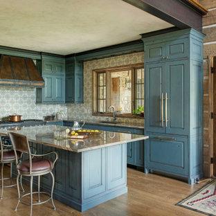 Modelo de cocina en L, rústica, con fregadero bajoencimera, armarios con paneles con relieve, puertas de armario azules, salpicadero multicolor, electrodomésticos con paneles, suelo de madera en tonos medios, una isla, suelo marrón y encimeras grises