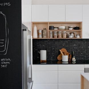 Modelo de cocina escandinava con armarios con paneles lisos, puertas de armario blancas, salpicadero negro y suelo negro