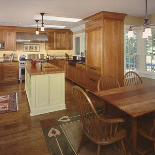 Mid-sized rustic eat-in kitchen designs - Example of a mid-sized mountain style u-shaped medium tone wood floor eat-in kitchen design in New York with wood countertops, medium tone wood cabinets, a farmhouse sink, shaker cabinets, white backsplash, porcelain backsplash, paneled appliances and an island
