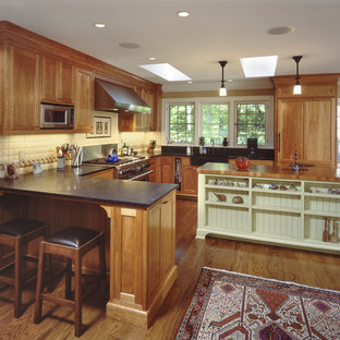 Inspiration for a mid-sized timeless u-shaped medium tone wood floor eat-in kitchen remodel in New York with paneled appliances, wood countertops, a farmhouse sink, shaker cabinets, medium tone wood cabinets, white backsplash, porcelain backsplash and an island