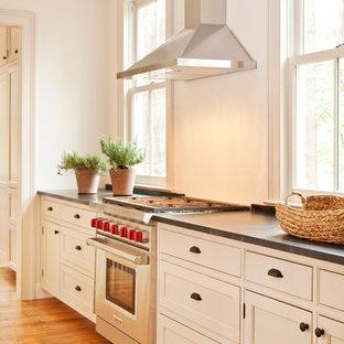 Неиссякаемый источник вдохновения для домашнего уюта: линейная кухня среднего размера в стиле кантри с обеденным столом, врезной раковиной, фасадами в стиле шейкер, белыми фасадами, столешницей из талькохлорита, белым фартуком, техникой из нержавеющей стали, паркетным полом среднего тона, островом и коричневым полом