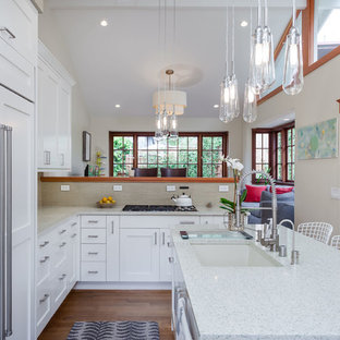 Mid-sized transitional l-shaped eat-in kitchen in San Francisco with an undermount sink, shaker cabinets, white cabinets, recycled glass benchtops, glass tile splashback, medium hardwood floors, with island, beige splashback and panelled appliances.