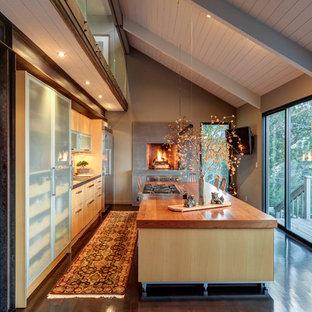 Inredning av ett eklektiskt mellanstort linjärt kök med öppen planlösning, med en nedsänkt diskho, släta luckor, skåp i ljust trä, träbänkskiva, stänkskydd med metallisk yta, mörkt trägolv och en köksö