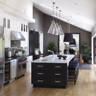 Traditional galley kitchen/diner in San Francisco with stainless steel appliances, metro tiled splashback, brown splashback, shaker cabinets, black cabinets, marble worktops, a submerged sink, white worktops, light hardwood flooring, an island and beige floors.