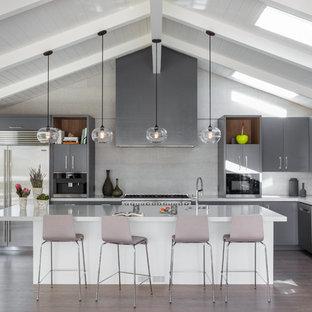 Idée de décoration pour une grand cuisine ouverte marine en L avec un évier 1 bac, un placard à porte plane, des portes de placard grises, une crédence grise, un électroménager en acier inoxydable, un sol en bois foncé, un îlot central, un sol marron, un plan de travail en quartz modifié et une crédence en carreau de céramique.