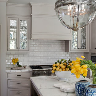 This is an example of a traditional kitchen in San Francisco with marble benchtops, beaded inset cabinets, grey cabinets, white splashback and subway tile splashback.