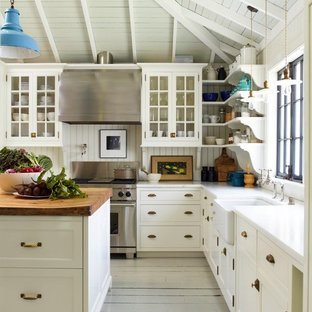 Large rural l-shaped kitchen in San Francisco with a belfast sink, recessed-panel cabinets, white cabinets, wood worktops, white splashback, stainless steel appliances, painted wood flooring and an island.