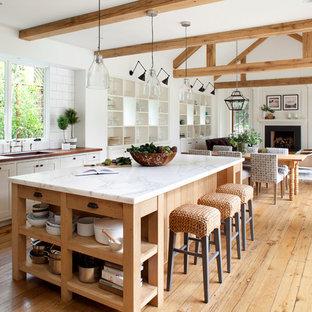 Imagen de cocina de estilo de casa de campo, abierta, con fregadero bajoencimera, armarios abiertos, puertas de armario blancas, salpicadero blanco, salpicadero de azulejos tipo metro, suelo de madera en tonos medios y una isla
