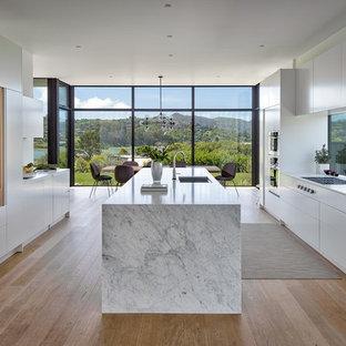 サンフランシスコの大きいモダンスタイルのおしゃれなキッチン (アンダーカウンターシンク、フラットパネル扉のキャビネット、白いキャビネット、大理石カウンター、パネルと同色の調理設備、淡色無垢フローリング、白いキッチンカウンター、ガラスまたは窓のキッチンパネル、ベージュの床) の写真