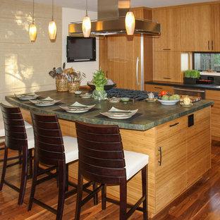 サンフランシスコのアジアンスタイルのおしゃれなキッチン (アンダーカウンターシンク、フラットパネル扉のキャビネット、中間色木目調キャビネット、御影石カウンター、黒いキッチンパネル、石スラブのキッチンパネル、パネルと同色の調理設備) の写真