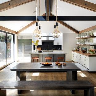 На фото: кухни в морском стиле с обеденным столом, плоскими фасадами, белыми фасадами, черным фартуком, техникой из нержавеющей стали, паркетным полом среднего тона, островом, серой столешницей, балками на потолке и сводчатым потолком