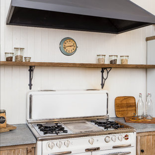 Small rustic enclosed kitchen appliance - Example of a small mountain style light wood floor enclosed kitchen design in San Francisco with a farmhouse sink, medium tone wood cabinets, white backsplash, wood backsplash, white appliances and an island