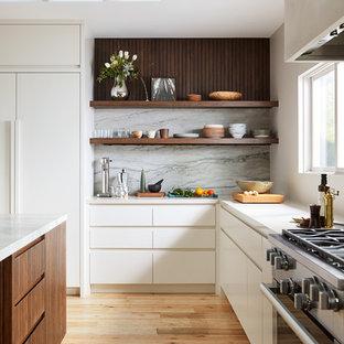 サンフランシスコの北欧スタイルのおしゃれなキッチン (シングルシンク、フラットパネル扉のキャビネット、白いキャビネット、緑のキッチンパネル、石スラブのキッチンパネル、淡色無垢フローリング、白いキッチンカウンター、シルバーの調理設備の) の写真