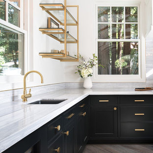Design ideas for a mid-sized transitional u-shaped eat-in kitchen in San Francisco with panelled appliances, black cabinets, marble benchtops, grey splashback, with island, an undermount sink, open cabinets, stone slab splashback, medium hardwood floors and beige floor.