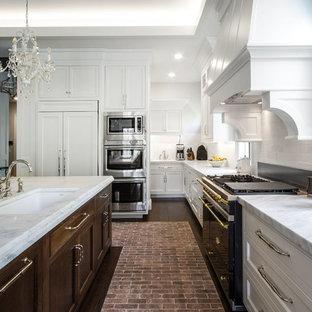 Idéer för ett stort amerikanskt kök, med en undermonterad diskho, skåp i shakerstil, vita skåp, marmorbänkskiva, vitt stänkskydd, stänkskydd i tunnelbanekakel, rostfria vitvaror, tegelgolv och en köksö