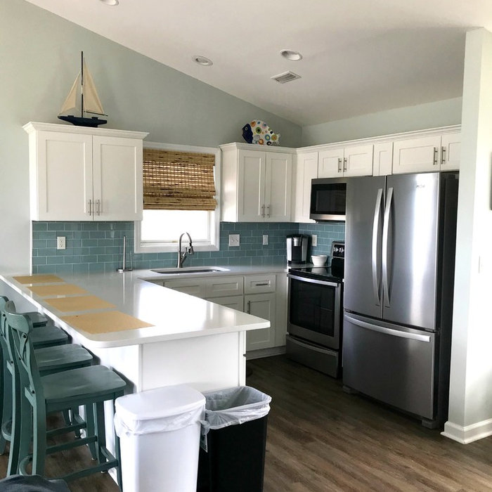 Mid-sized beach style u-shaped dark wood floor and brown floor eat-in kitchen photo with an undermount sink, shaker cabinets, white cabinets, blue backsplash, subway tile backsplash, stainless steel a