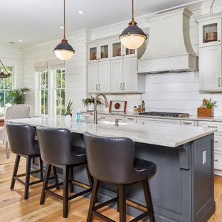 他の地域の広いトランジショナルスタイルのおしゃれなキッチン (エプロンフロントシンク、御影石カウンター、白いキッチンパネル、木材のキッチンパネル、茶色い床、白いキッチンカウンター、シェーカースタイル扉のキャビネット、白いキャビネット、無垢フローリング) の写真