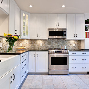 This is an example of a mid-sized traditional u-shaped eat-in kitchen in Atlanta with stainless steel appliances, recessed-panel cabinets, white cabinets, soapstone benchtops, a farmhouse sink, multi-coloured splashback, glass tile splashback, porcelain floors, beige floor, with island and green benchtop.