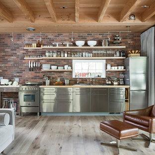 オースティンのカントリー風おしゃれなキッチン (ダブルシンク、フラットパネル扉のキャビネット、ステンレスキャビネット、木材カウンター、赤いキッチンパネル、レンガのキッチンパネル、シルバーの調理設備の、淡色無垢フローリング、ベージュの床、ベージュのキッチンカウンター) の写真